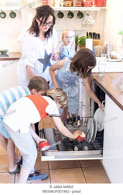 Mother and four children loading the dishwasher