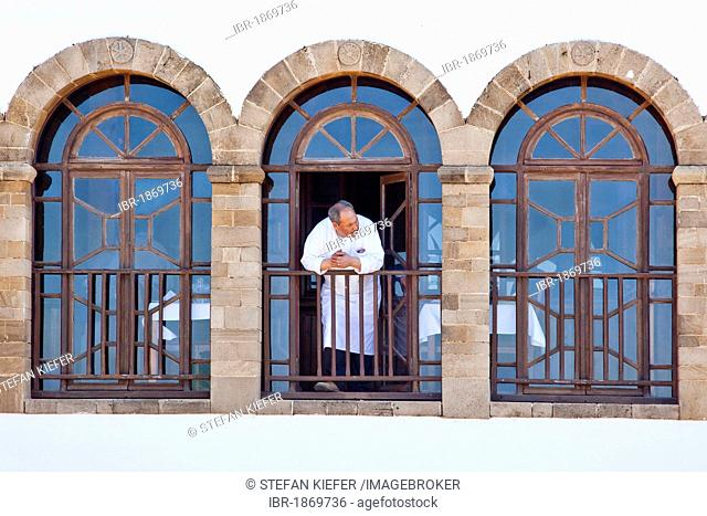 Chef looking out of the window of a restaurant in the historic town or medina, UNESCO World Heritage Site, Essaouira, Morocco, Africa