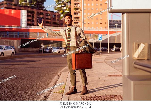 Businessman hailing transport on pavement, Milano, Lombardia, Italy