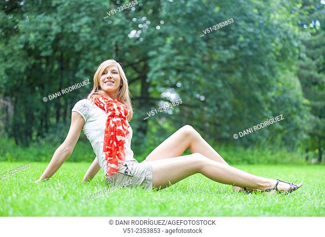 Blonde beautiful woman sittin in the park in Spring