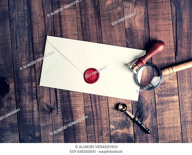 Old envelope with red wax seal, magnifier and stamp on wood table background. Flat lay