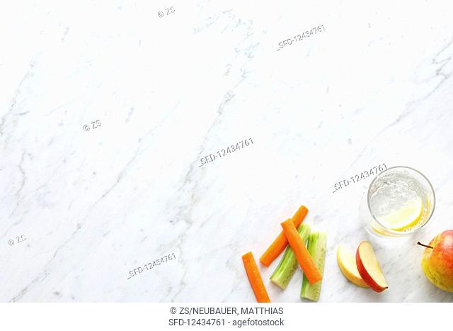 Sliced fruit and vegetables and a glass of mineral water