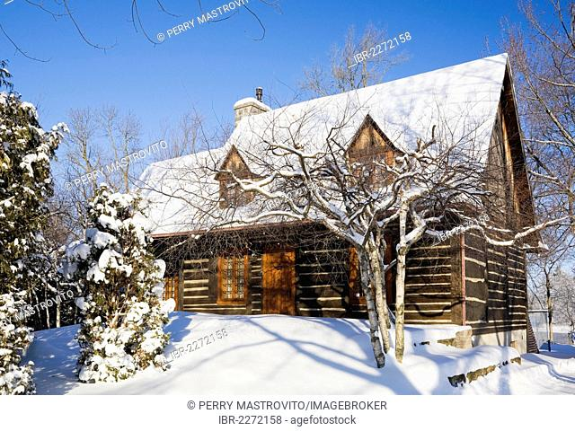 Old reconstructed Canadiana cottage-style residential log home, 1975, in winter, Quebec, Canada. This image is property released for book, calendar, magazine