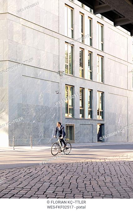 Mature businessman riding bicycle in the city