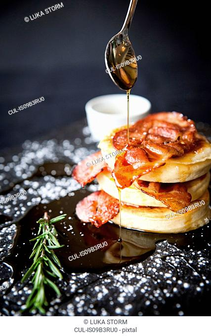 Breakfast bacon crumpet with maple syrup pouring from spoon onto slate