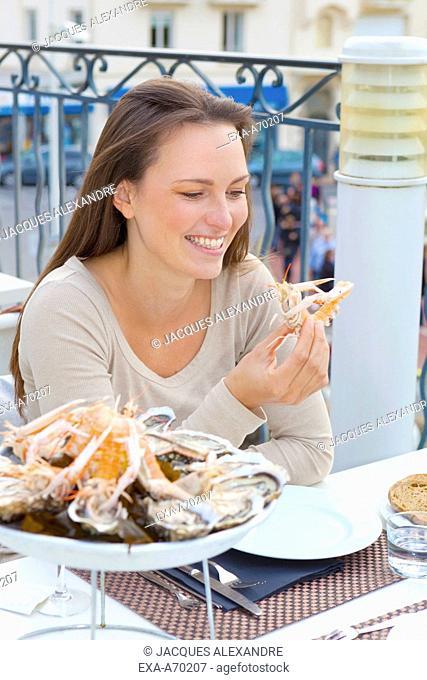 Woman eating seafood outside