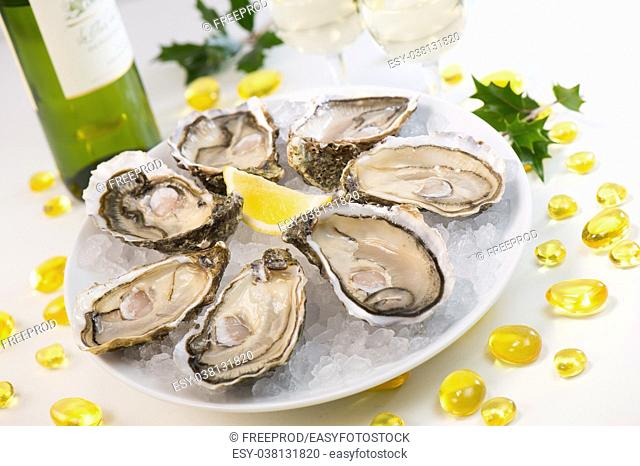 Oysters on ice and with a piece of lemon and wine bottle and glass