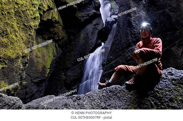 Woman in rocky valley with waterfall