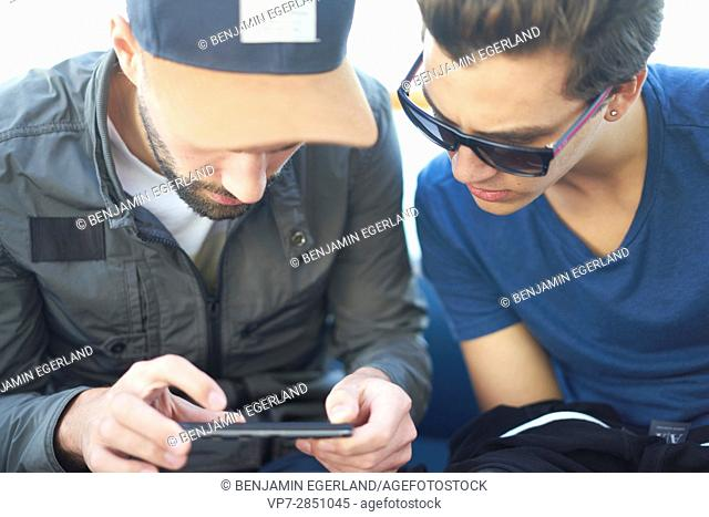 two concentrated young males using mobile device intensely