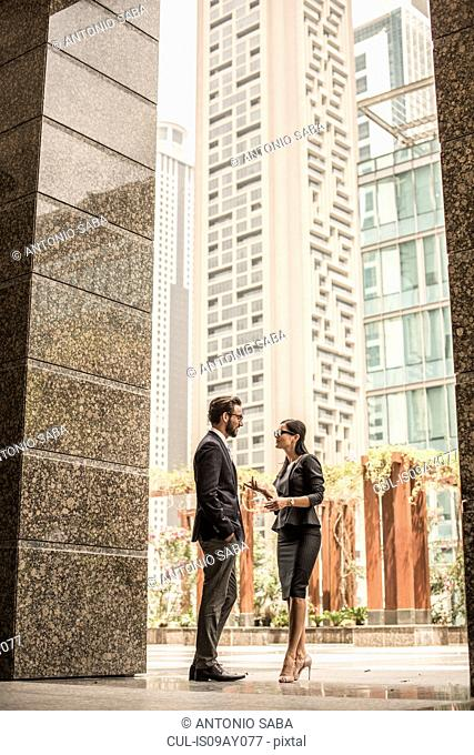 Businessman and woman talking outside office, Dubai, United Arab Emirates