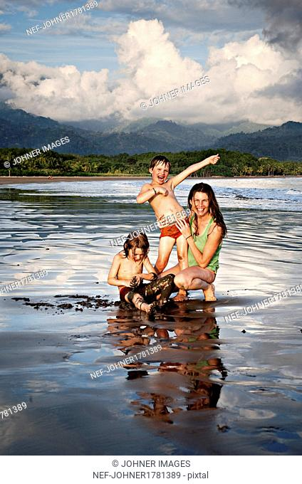 Mother with two sons on beach