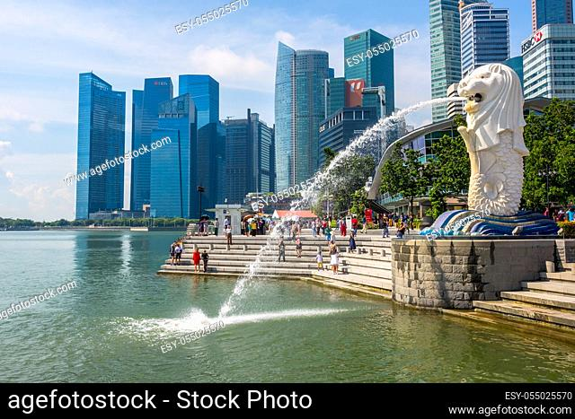 Sunny day. The Merlion Fountain in the background of skyscrapers and tourists. Editorial use only
