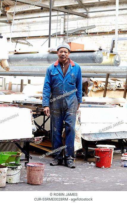 Portrait of man wearing boiler suit in screen printing factory
