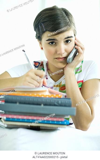 Teen girl with stack of homework, using cell phone and writing in notebook