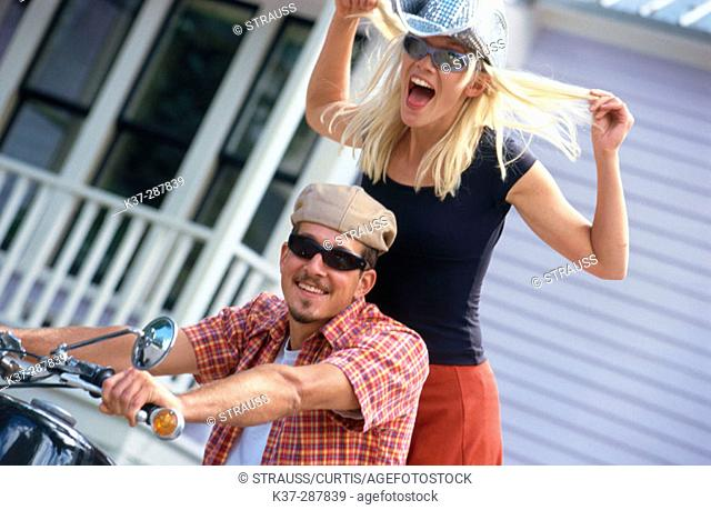 Young couple on motor cycle in urban setting