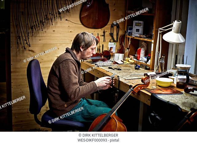 Violin maker in his workshop filing a cello mechanism