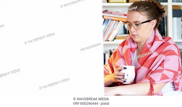 Woman using a laptop while having cup of coffee