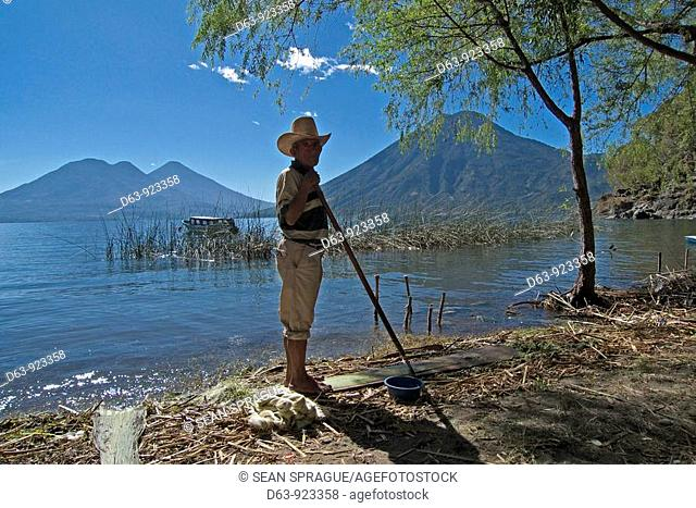 Guatemala. Man cleaning garbage from beach, San Marcos la Laguna, Lake Atitlan