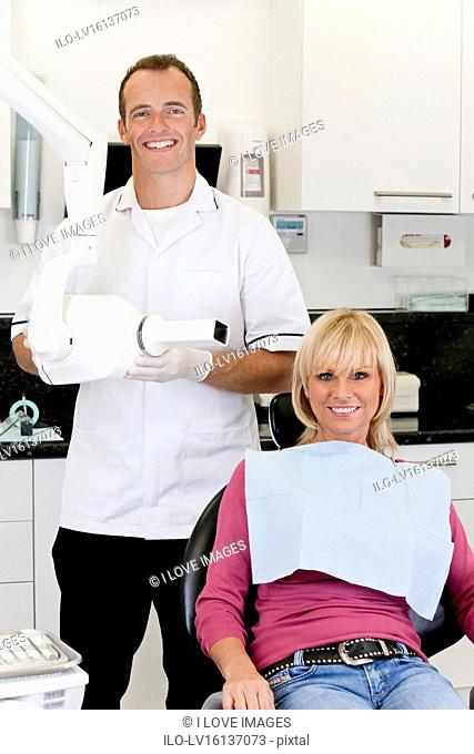 A male dentist with a female patient in his surgery
