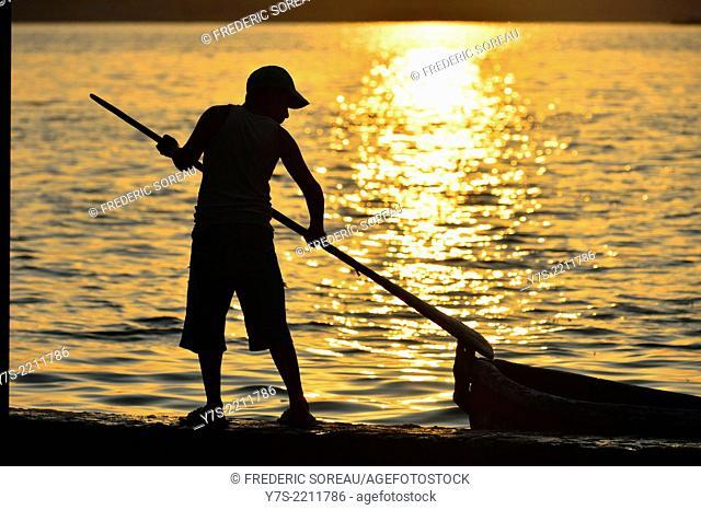 Sunset silhouette of boy , El Peten, Flores, Lago de Peten Itza, Guatemala, Central America