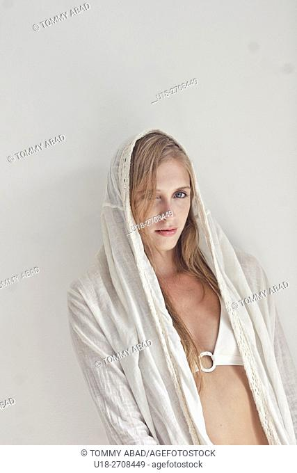 blonde woman with white tunica and white bikini / white background