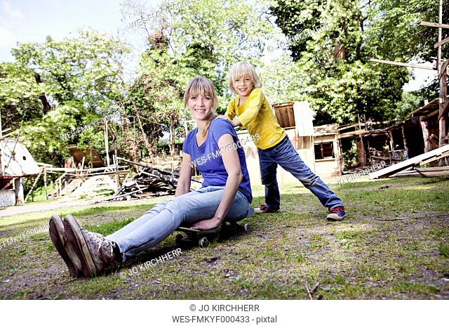 Germany, North Rhine Westphalia, Cologne, Mother and son playing with skateboard, smiling