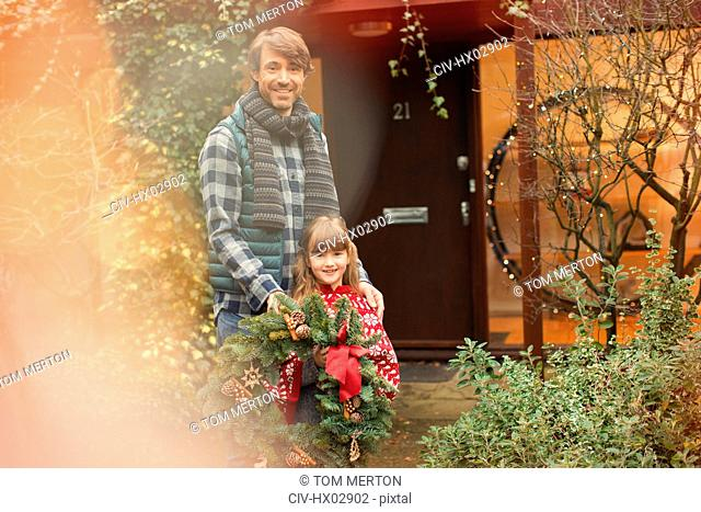 Portrait smiling father and daughter holding Christmas wreath outside house