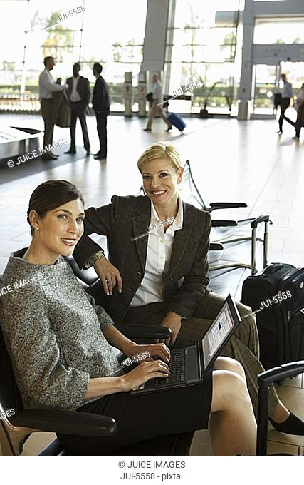 Two businesswomen waiting in airport departure lounge, woman using laptop, smiling, side view, portrait
