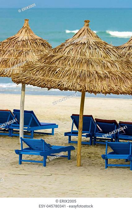 Palm shelters and sunbeds at the China Beach in Da Nang, in Vietnam. It is also called Non Nuoc Beach. South China Sea on the background