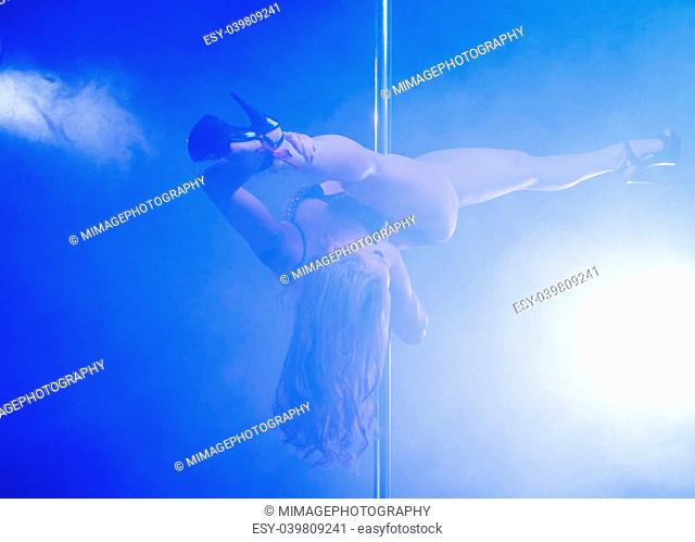 Portrait of a sensual female pole dancer performing with legs open