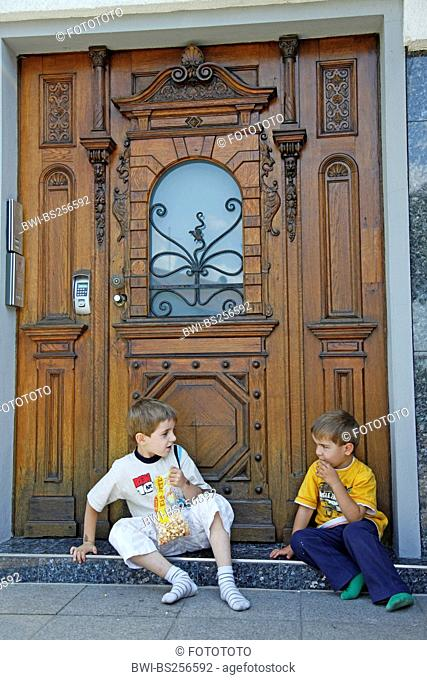 two boys sitting in front of entry door and eating popcorn