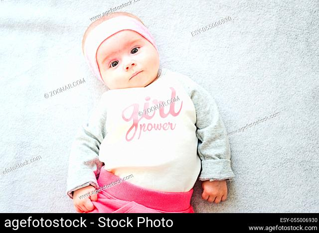 6 months old baby girl lie on a couch in bright sunny living room. Infant concept
