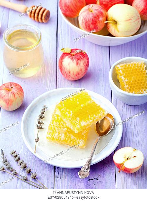 Honey, honeycombs and fresh apples on a lavender wooden background Top view