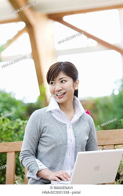 Woman Using Laptop on Bench