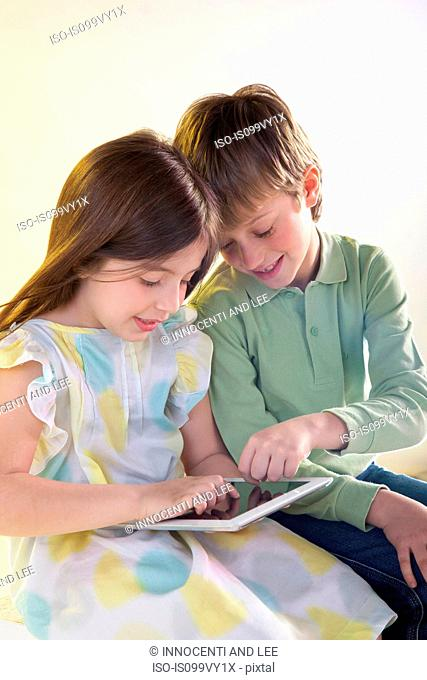 Girl and boy using digital tablet