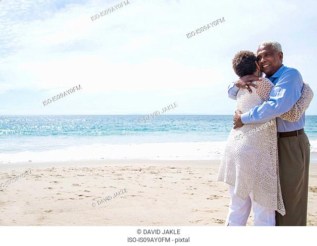 Senior couple on beach, hugging, smiling