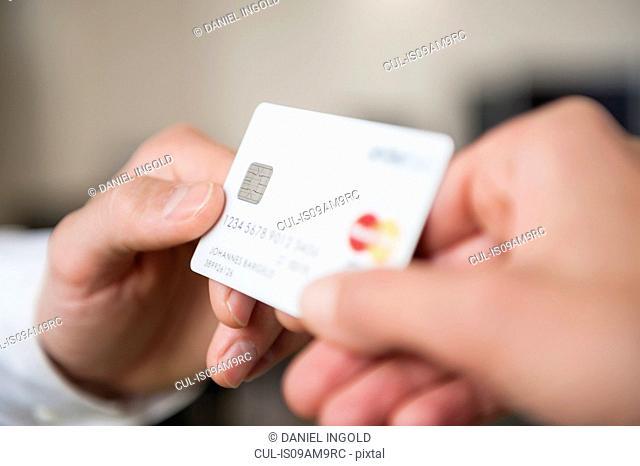 Man passing credit card to woman, close-up