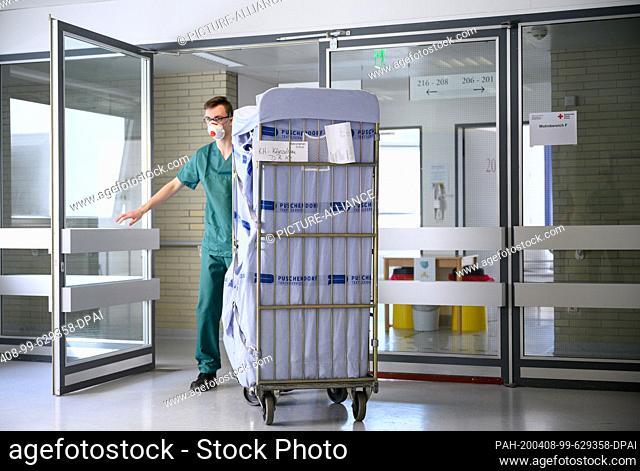 06 April 2020, Baden-Wuerttemberg, Künzelsau: In an isolation ward in a former clinic, an employee pushes a cart through a door