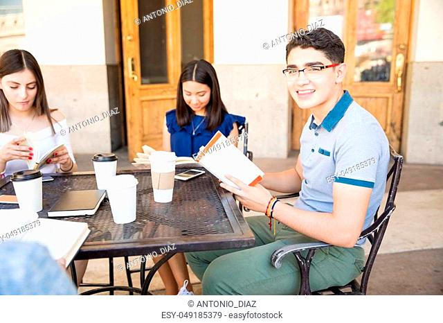 Portrait of handsome young man at outdoors cafe reading book with friends sitting around the table