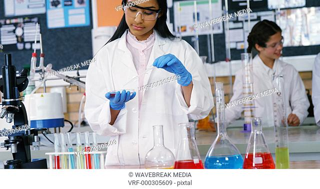 School girl experimenting with chemical in laboratory at school