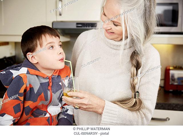 Grandmother offering grandson drink