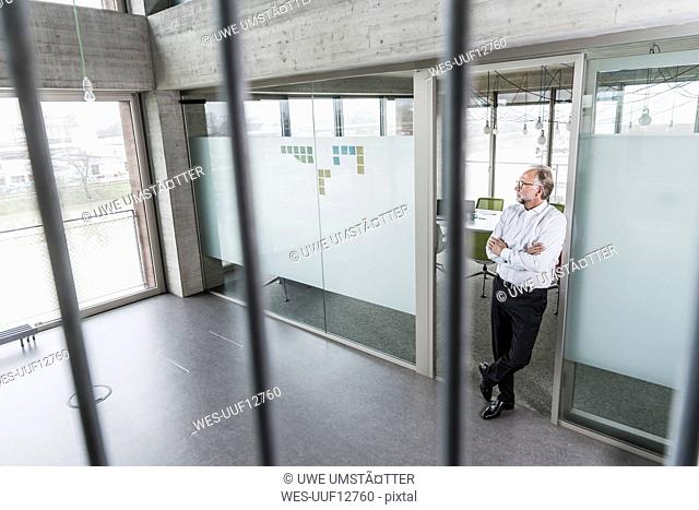 Mature businessman standing in office thinking