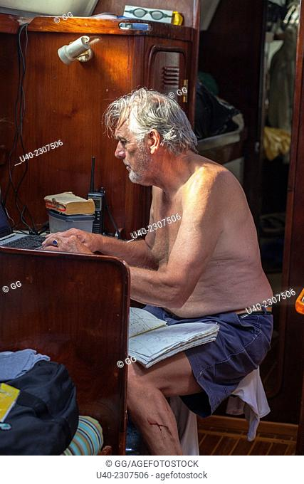 Captain checking charts on sailboat, Belize