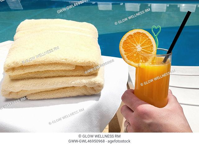 Person's hand holding a glass of orange juice