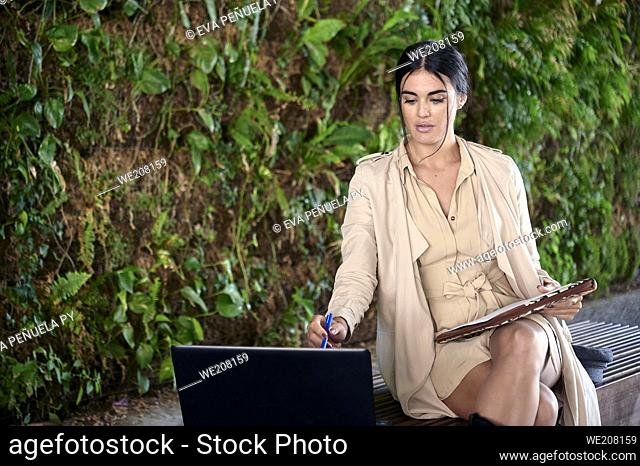 Carefree and serene young European woman using her laptop while sitting in the urban park