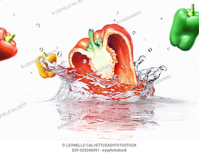Sweet bell peppers multicolors falling and splashing into clear water. On white background