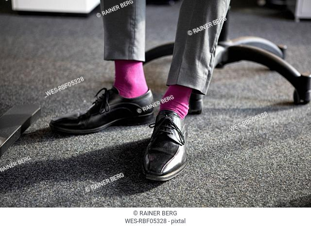 Close-up of businessman in office wearing pink socks