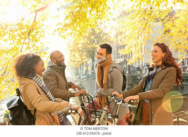 Smiling young couple friends with bicycles talking under sunny autumn tree