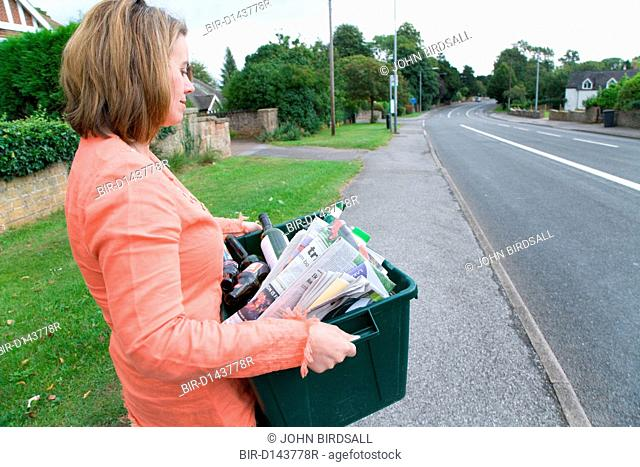 Woman carrying curb side recycling collection box out onto the pavement ready for collection