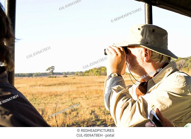Senior man looking out through binoculars on safari, Kafue National Park, Zambia